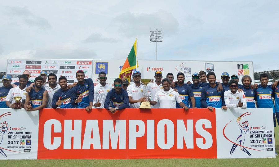 Sri Lankan cricketers pose for photographers after victory