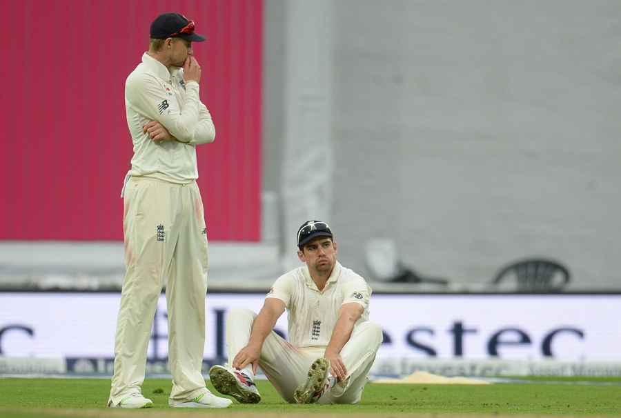 Alastair Cook of England reacts with Joe Root after dropping Shai Hope