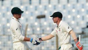 Australian cricketer David Warner (R) shakes hand with teammate Peter Handscomb