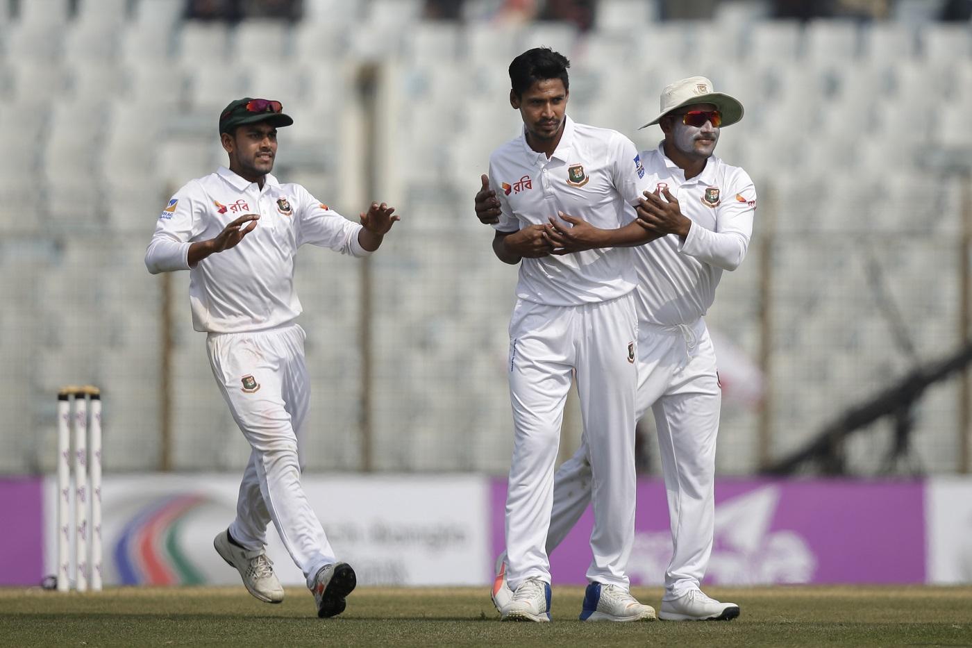 Bangladesh's Mustafizur Rahman, center, celebrate with his teammates Imrul Kayes, and Mehidy Hasan