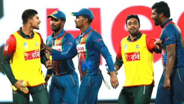 Bangladesh's Nurul Hasan, right, exchanges words with Sri Lanka's skipper Thisara Perera