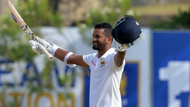Sri Lankan cricketer Dimuth Karunaratne raises his bat and helmet in celebration after scoring a century
