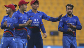 Afghanistan's Rashid Khan, right, leaves the field with teammates after their win