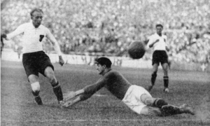 Matthias Sindelar lifts the ball over the Belgian goalkeeper to make it 3-0 during Austria's 4-1 win over Belgium during their June 1933 friendly match in Vienna.